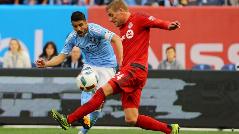 David Villa (left) fires a shot past Toronto's Damien Perquis