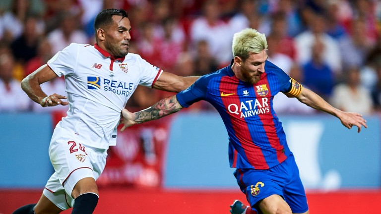Lionel Messi fends off Gabriel Mercado of Seville