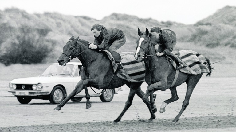 RED RUM (LEFT) GALLOPS ON THE SOUTHPORT BEACH RIDDEN BY HIS LAD, BILLY BEARDWOOD, WITH STABLE COMPANION, SILENT COMFORT. TRAINER, GINGER McCAIN IS IN THE CAR FOLLOWING CLOSE BEHIND, PICTURED 2 DAYS BEFORE GRAND NATIONAL.SOUTHPORT BEACH 1975.THIS PHOTOGRAP