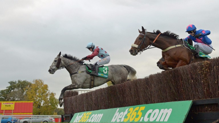 Irish Cavalier leads Cue Card on his way to winning the bet365 Charlie Hall Chase at Wetherby
