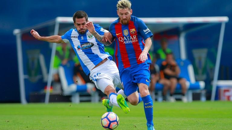 Leganes defender Pablo Insua (left) attempts to stop Lionel Messi
