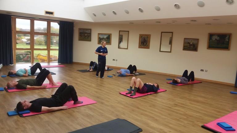 Physio Daloni Lucas takes a pilates class with Sam Twiston-Davies (maroon shorts)