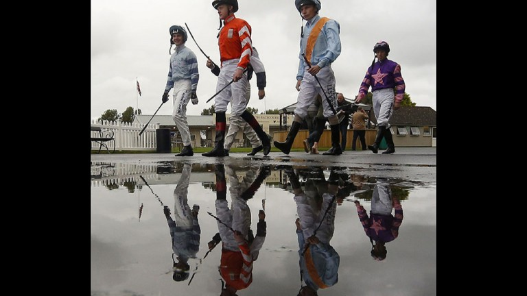 Seeing double: jockeys splash through the puddles on their way to the parade ring at Bath