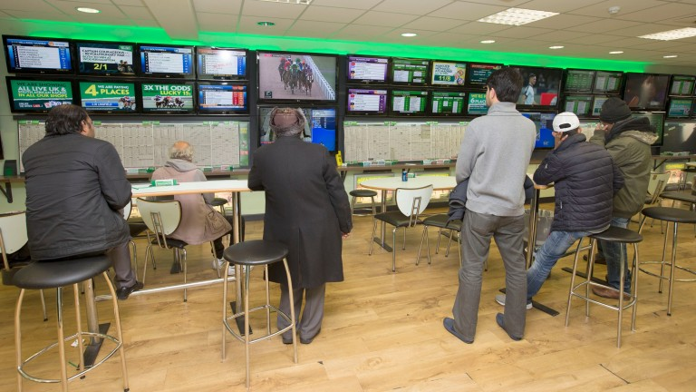 Punters watch the action on Tuesday at the Paddy Power shop in London's Commercial Road