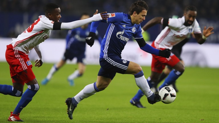 Yevhen Konoplyanka (blue) of Schalke fends off Hamburg's Gideon Jung