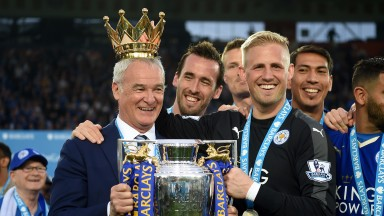 LEICESTER, ENGLAND - MAY 07:  Claudio Ranieri poses with the Premier League Trophy while Kasper Schmeichel puts the crown on the head of the manager as players and staffs celebrate the season champions after the Barclays Premier League match between Leice