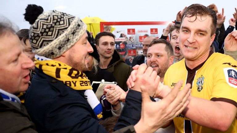Jamie Collins celebrates with Sutton fans after their win over Leeds