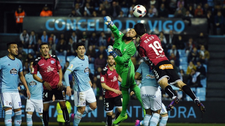 Celta Vigo goalkeeper Sergio 'Alvarez competes for the ball with Manu Garcia of Alaves