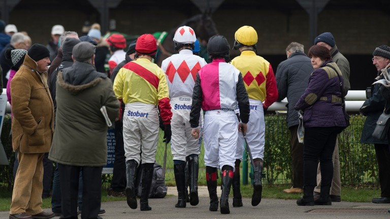 Let's go to work: jockeys walk into the paddock for the opening race at Huntingdon