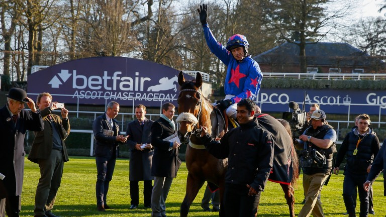 Celebration time: Paddy Brennan raises his arms aloft after Cue Card's ninth Grade 1 victory