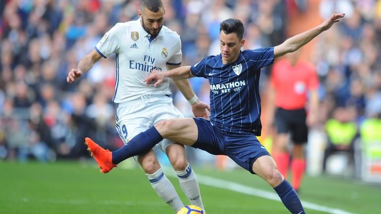 Malaga's Juanpi battles with Karim Benzema