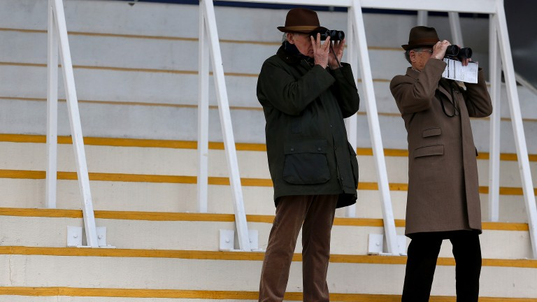 Zooming in: two racegoers use their binoculars to follow the action on the track