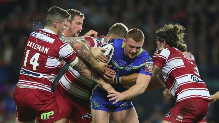 Warrington's Jack Hughes is wrapped up by the Wigan defence