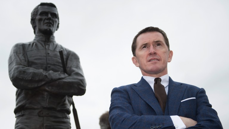 Spitting image: Sir Anthony McCoy poses in front of the statue of himself unveiled before racing