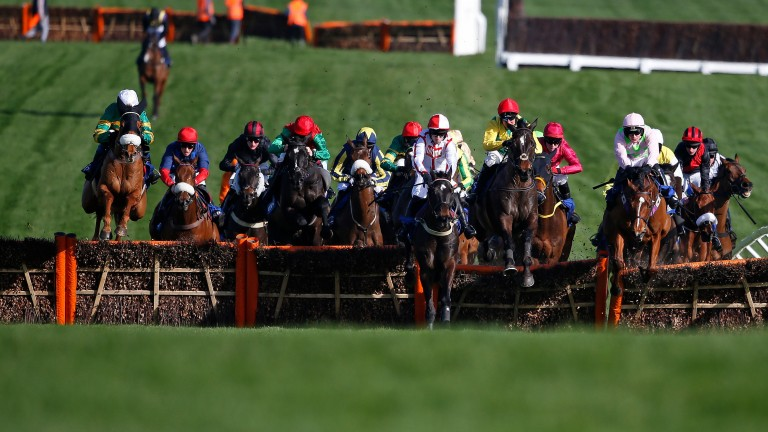 CHELTENHAM, ENGLAND - MARCH 15: Robbie Power riding Supasundae (C, yellow/red cap) clear the second last before winning The Coral Cup Handicap Hurdle Race at Cheltenham racecourse on day two of the festival meeting on March 15, 2017 in Cheltenham, England