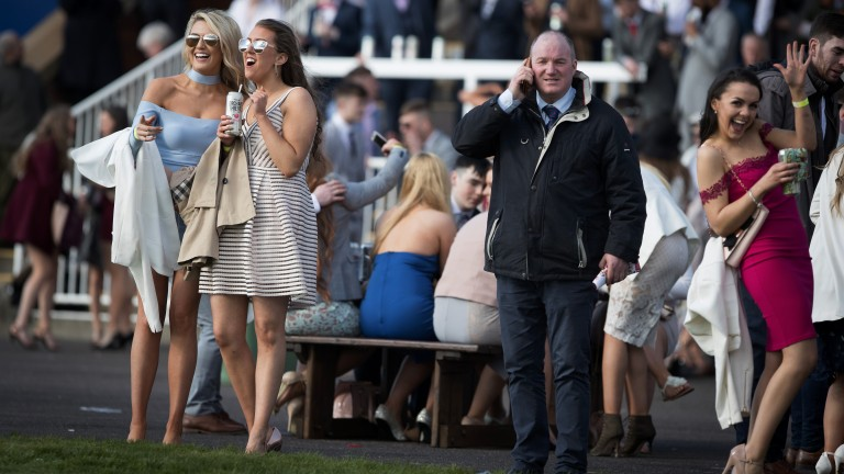 Mixed crowd: a punter talks on his phone as student racegoers enjoy their afternoon