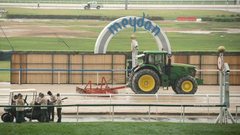 Groundstaff work on the course as heavy rain hit Meydan racecourse on Saturday morning