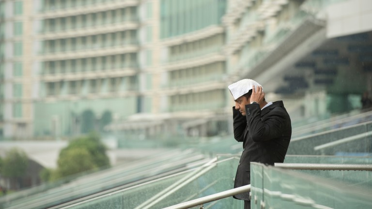 A man tries to shelter from the rain at Meydan