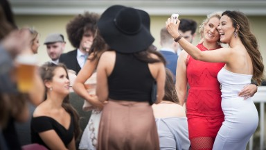 Posing for a picture: two racegoers smile for the camera with the annual student raceday attracting a big crowd at the track