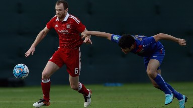 Mark Reynolds (left) of Aberdeen in action during a friendly match against Bunyodkor