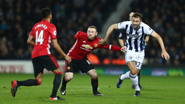 Wayne Rooney of Manchester United (C) and Gareth McAuley of West Brom (R) battle for possession