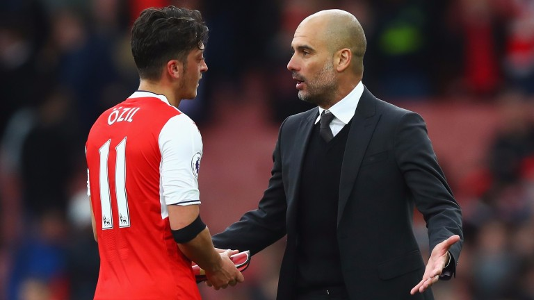 Mesut Ozil (left) chats with Pep Guardiola after Arsenal's 2-2 draw with Manchester City at the Emirates