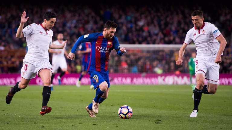 Lionel Messi of Barcelona takes on Seville