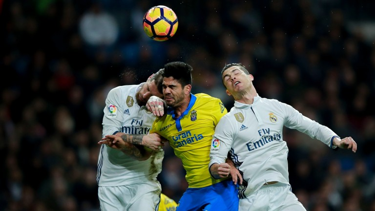 Aythami Artiles of Las Palmas is flanked by Sergio Ramos (left) and Cristiano Ronaldo of Real Madrid