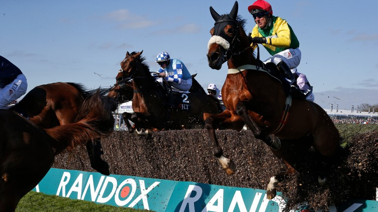 Bulldozer: Ploughing through a fence can't stop Fox Norton (right) from winning the Melling Chase