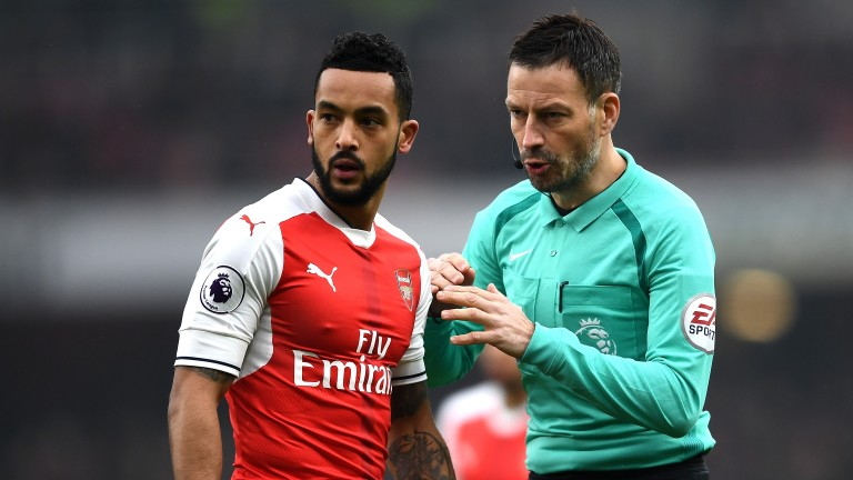 Referee Mark Clattenburg speaks to Theo Walcott