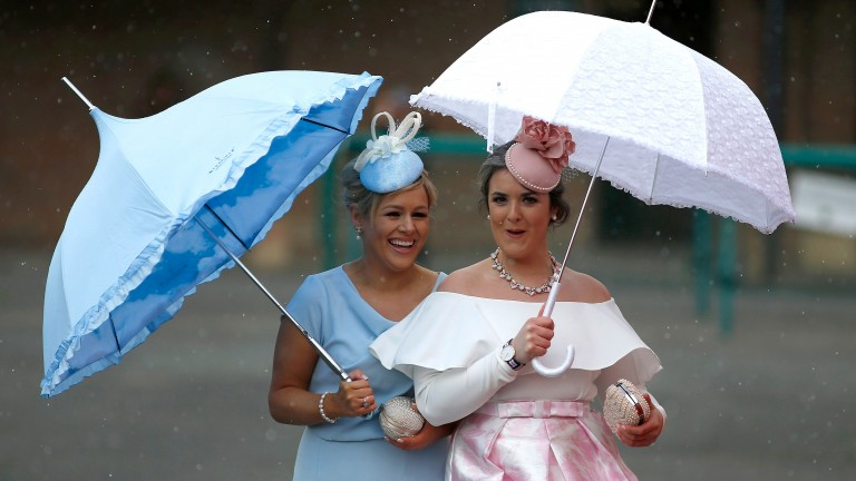 Two racegoers arrive in all their finery - and their umbrellas came in handy too