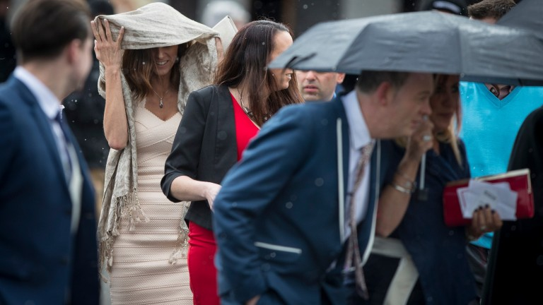 Racegoers arrives at the track on Tuesday to wind and hailstones
