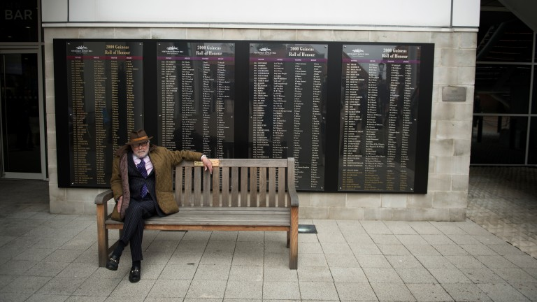 Illustrious company: one racegoer relaxes before racing in front of the 2,000 Guineas roll of honour