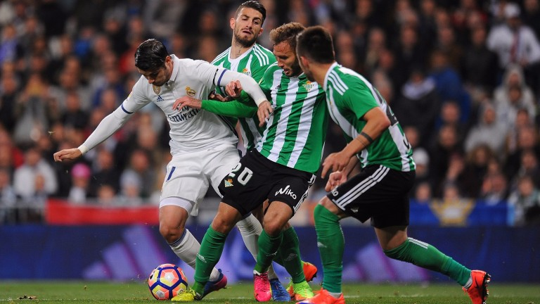 Real Betis players grapple with Real Madrid's Alvaro Morata