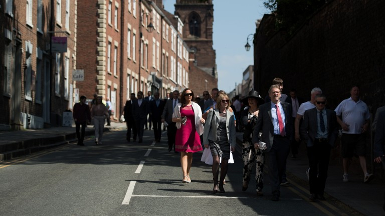 On the move: racegoers make their way through the streets to the track