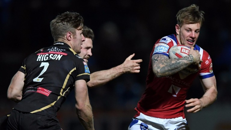 Tom Johnstone of Wakefield (right) evades the attentions of Leigh players