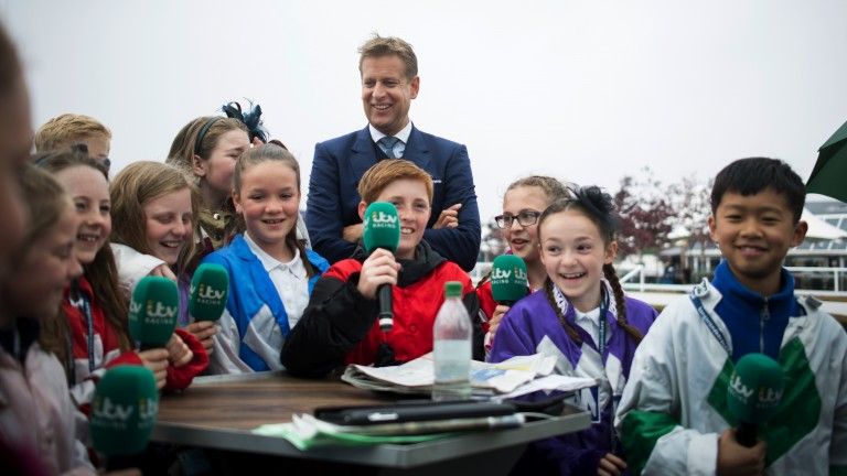 Child's play: ITV Racing presenter Ed Chamberlin was joined by a few intruders at Chester