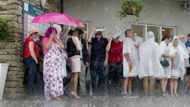 Racegoers takes shelter from the heavy rain at Cartmel