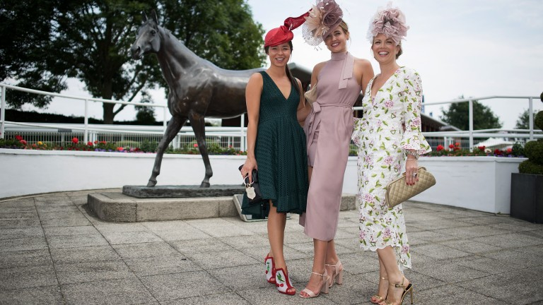 All dressed up: three racegoers pose for a photo on ladies' day on the Downs