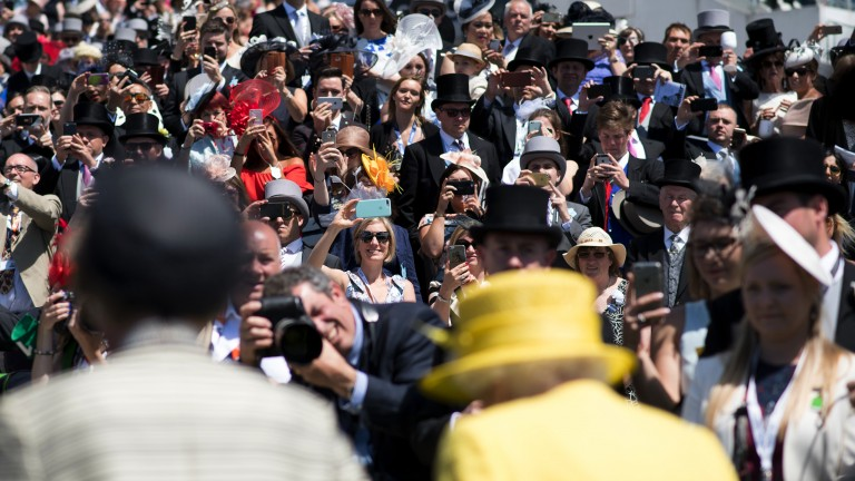 Royal reception: racegoers catch a glimpse of the Queen on her arrival at the track