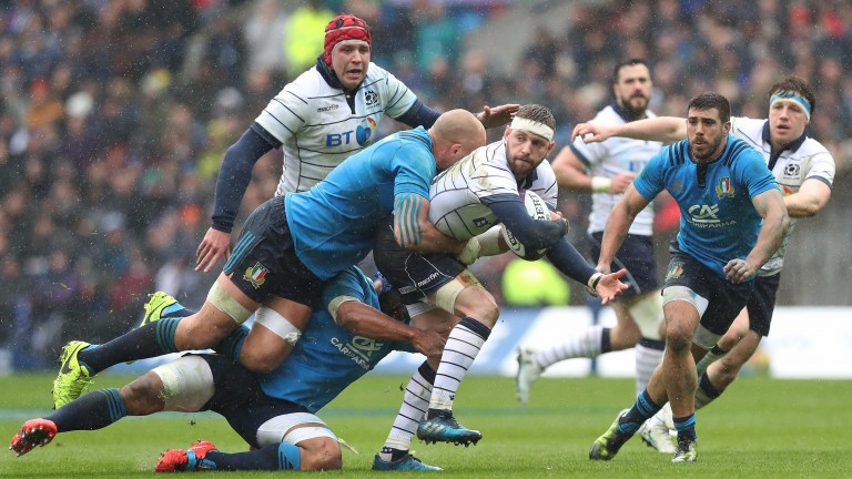 Finn Russell is tackled by Sergio Parisse in the Six Nations