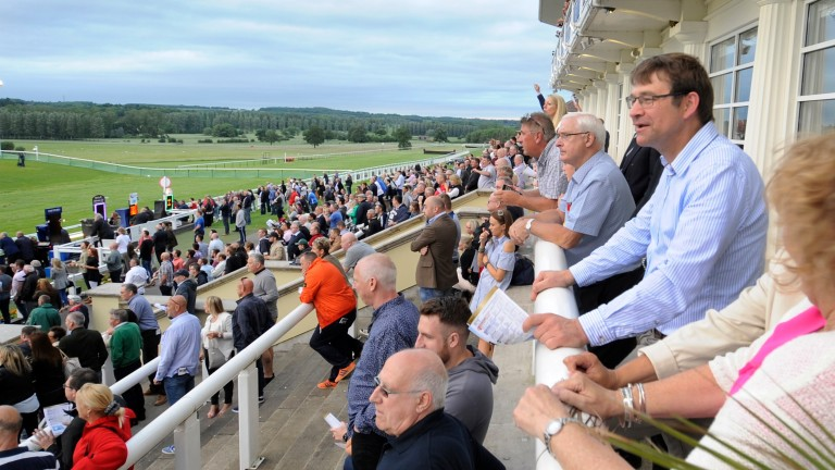 Racegoers watch the action from the restaurant balcony
