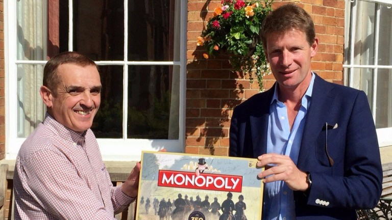 David Milnes presents Qatar Racing manager David Redvers with a signed edition of Newmarket Monopoly, which he auctioned to raise money for Allan Mackay