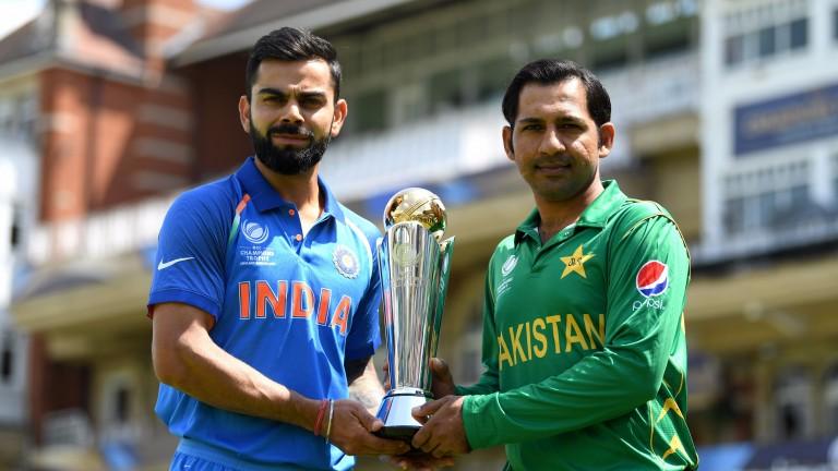 Captains Virat Kohli (left) and Sarfraz Ahmed pose with the trophy