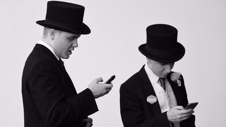 Patrons in the Royal Enclosure check their phones on Day Two of Royal Ascot