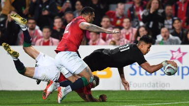 New Zealand winger Rieko Ioane scores the first of his two tries against the Lions