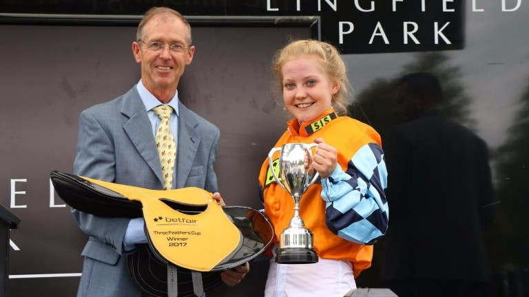 Elinor Jones receives her trophy from Derby-winning jockey John Reid after landing the Betfair Three Feathers Cup charity race for stable staff at Lingfield