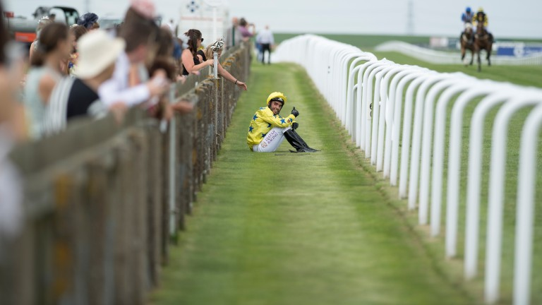 Sheikh Fahad, last year's winner, let's onlookers know he is not seriously hurt after his fall from Almagest