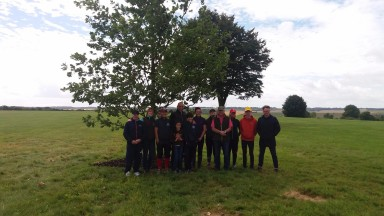 Oliver Sherwood and his team pose by the memorial tree for Many Clouds