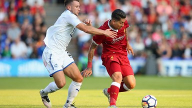 Tranmere's Liam Ridehalgh (left) gets to grips with Roberto Firmino of Liverpool